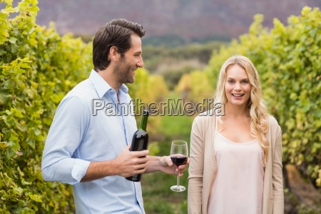 young happy man offering wine to