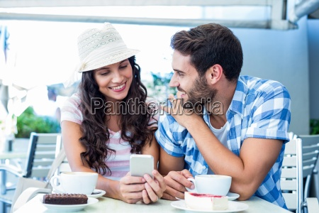 cute couple sitting in cafe looking