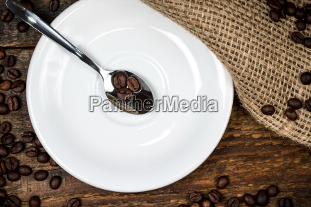 coffee beans on spoon with white
