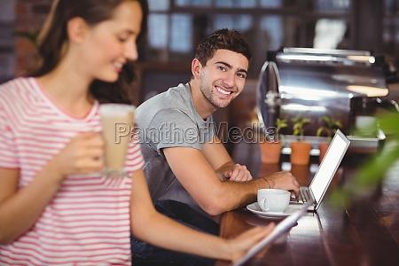 smiling young man sitting at bar