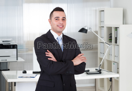 handsome businessman standing arms crossed