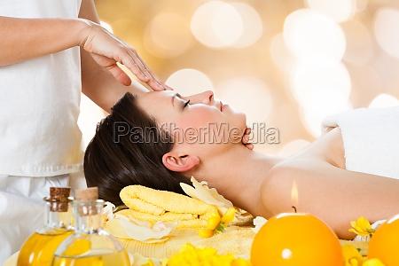 woman receiving head massage from massager