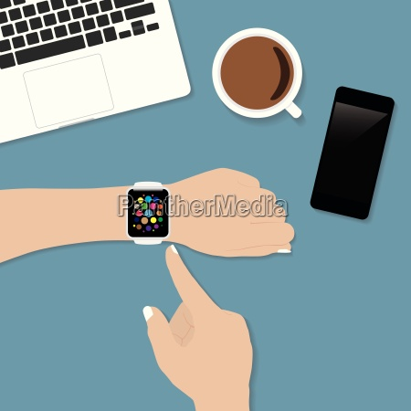 hand using smart watch on desk