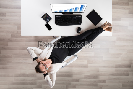 businesswoman relaxing on chair in office
