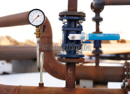blue valve and manometer on rusty