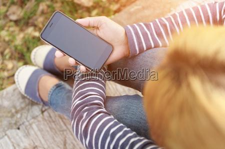 hipster female holding smart phone modern