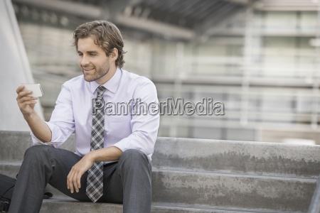 a man sitting holding a smart