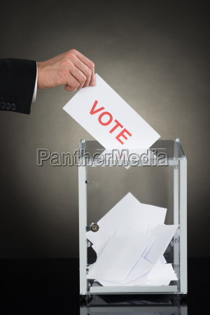 businessperson hand putting vote into a
