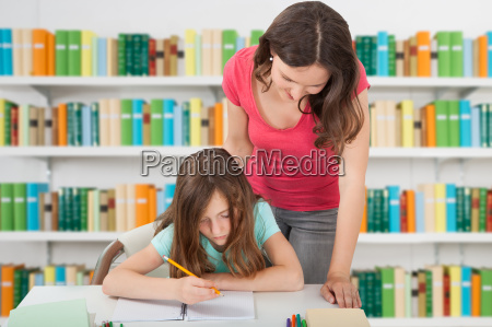 teacher assisting girl at school library