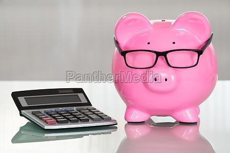 piggybank with eyeglasses and calculator