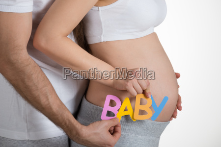 pregnant woman with husband holding text