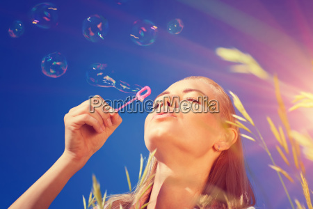 pretty woman blowing soap bubbles