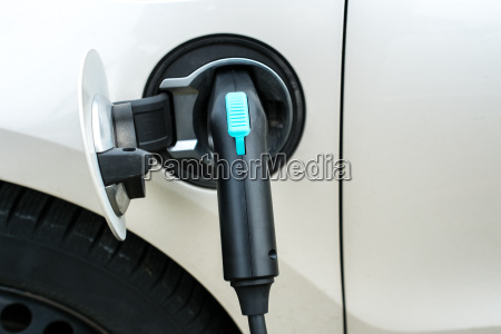 plug charges an electric car on