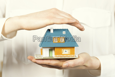 hand hovering small family house home