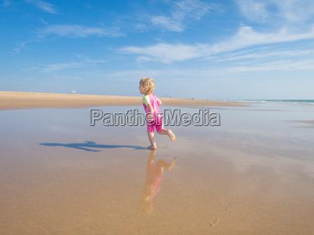 baby running at shore