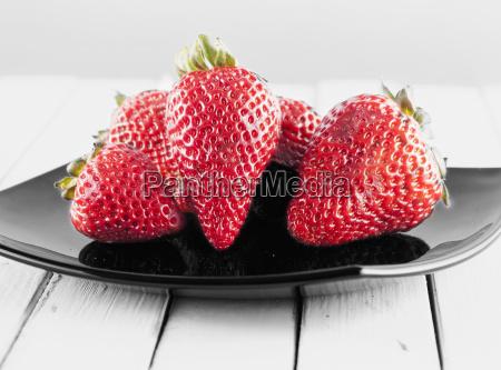 strawberries over black plate