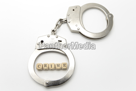 handcuffs with word crime on wooden