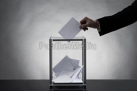 hand putting ballot in glass box