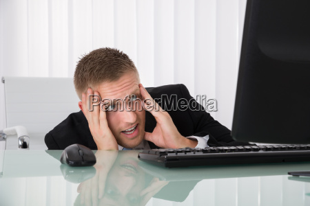 frightened businessman looking at computer