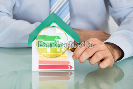 businessman with house model and magnifying