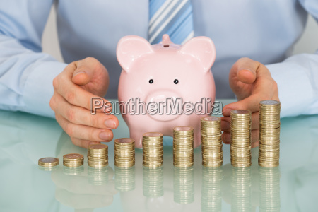businessman covering piggy bank