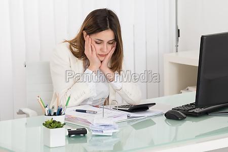 depressed businesswoman calculating invoice