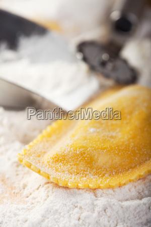 closeup of ravioli on flour