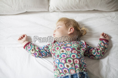 baby sleeping on white bed