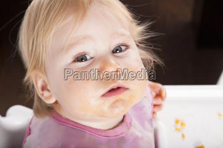 baby eating looking at camera