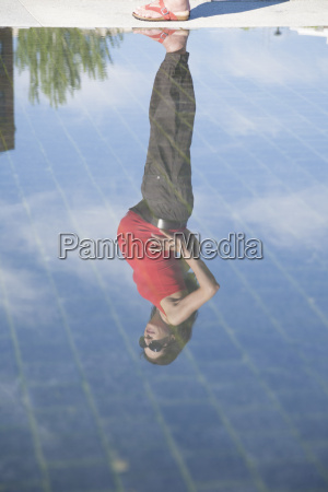 red shirt pregnant reflected on water