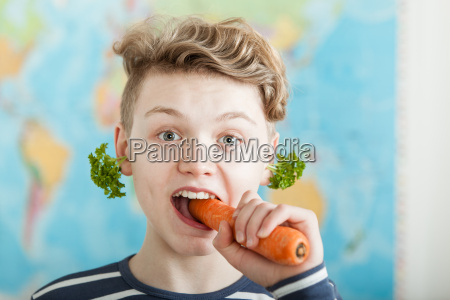 boy biting into large carrot in