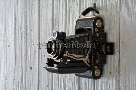 old camera hangs on old white