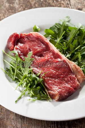 raw steak on rocket salad