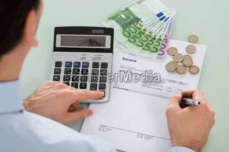 businessman examining invoice with money at
