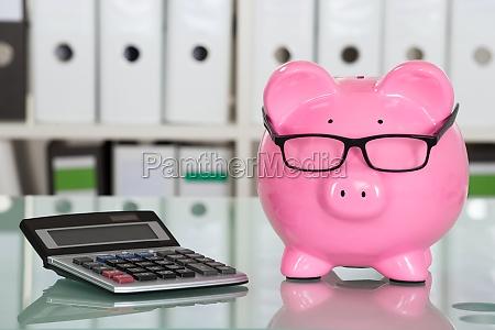 piggybank wearing eyeglasses and calculator on