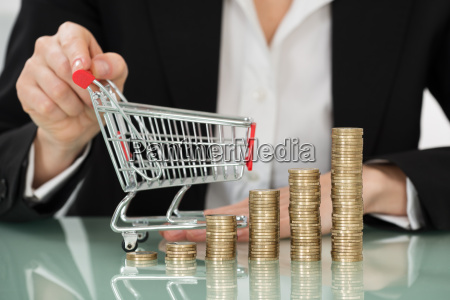 shopping trolley with stacked coins on