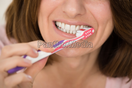 woman brushing teeth with toothbrush