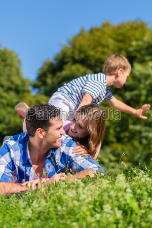 family is sitting on the meadow