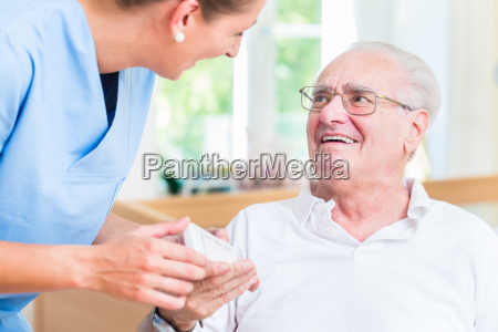 geriatryczne pielegniarka trzymajac reke starszym w