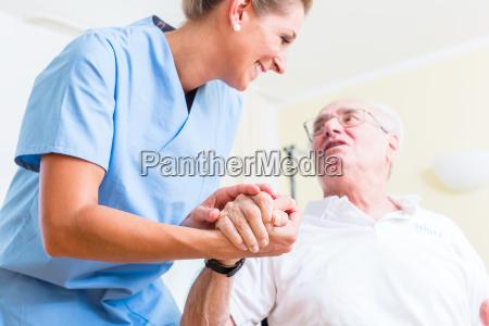 senior nurse holding hand from senior