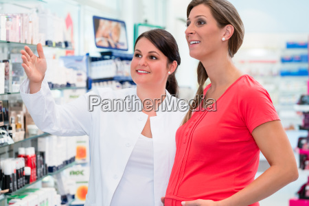pharmacist showing pregnant woman medication