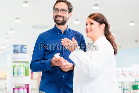 pharmacist advises customer in drugstore or