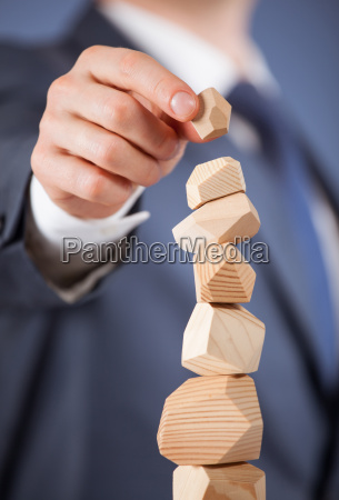 unrecognizable businessman forming a wooden pyramid