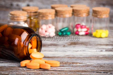 orange pills in glass container with
