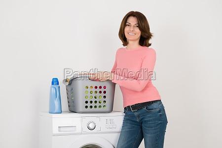 young woman standing by washing machine