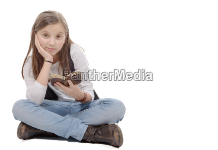 preteen girl reads a book sitting