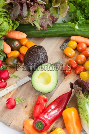 fresh vegetables around rustic cutting board