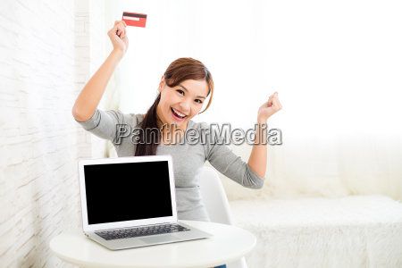 excited, woman, holding, credit, card, with - 16324573