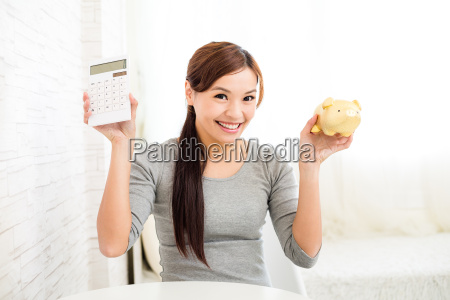 woman, showing, calculator, and, piggy, bank - 16324549