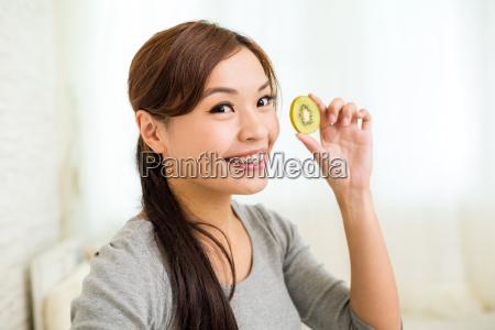 woman, showing, slices, of, kiwi, fruit - 16324539
